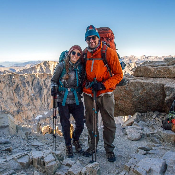 Megan and Michael wearing their backpacking packs. They are smiling and there are mountain peaks in the distance
