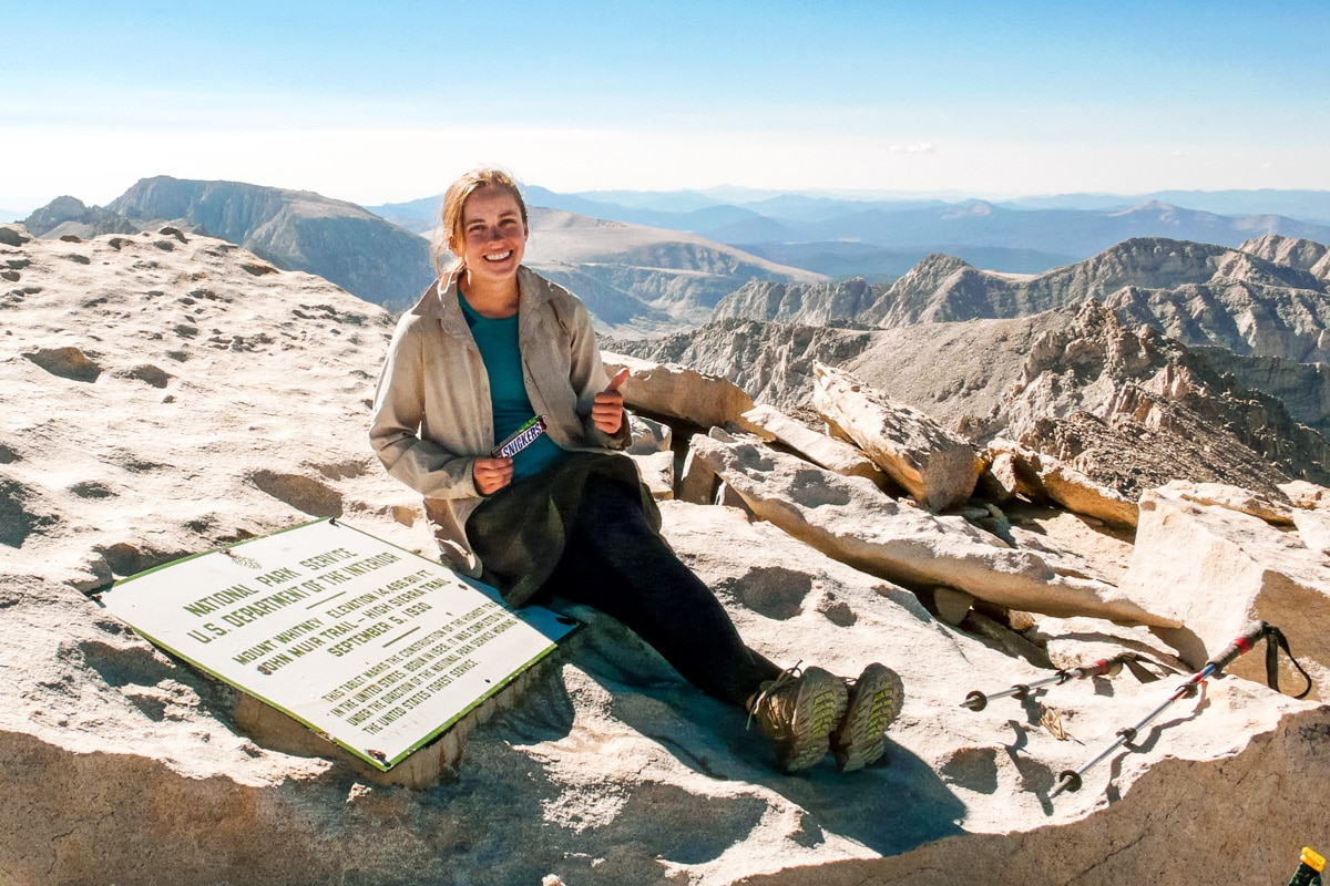 Megan holding a Snickers bar on the summit of Mt. Whitney