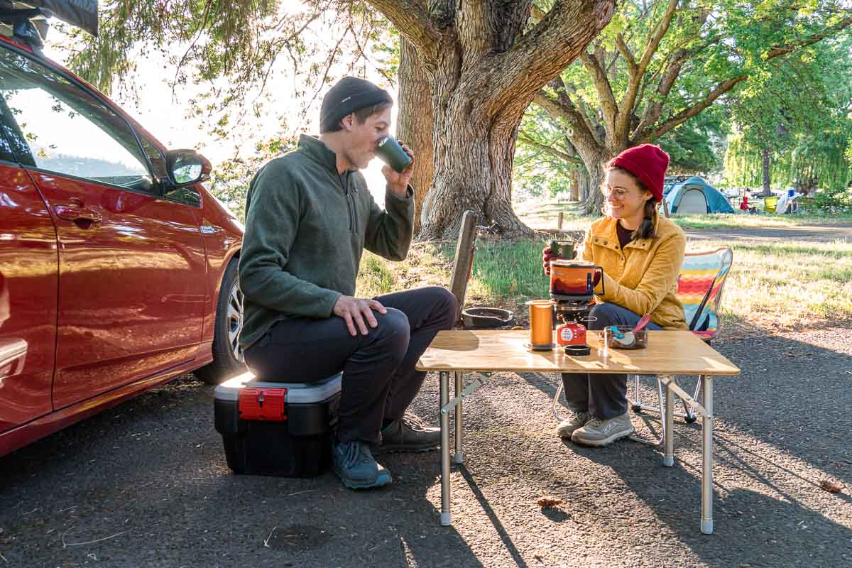 Megan and Michael sit at a small camping table and are drinking cups of coffee.