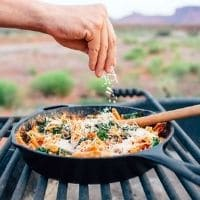 A hand sprinkling cheese into a cast iron skillet.