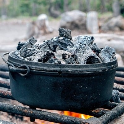 A Dutch oven with coals on top