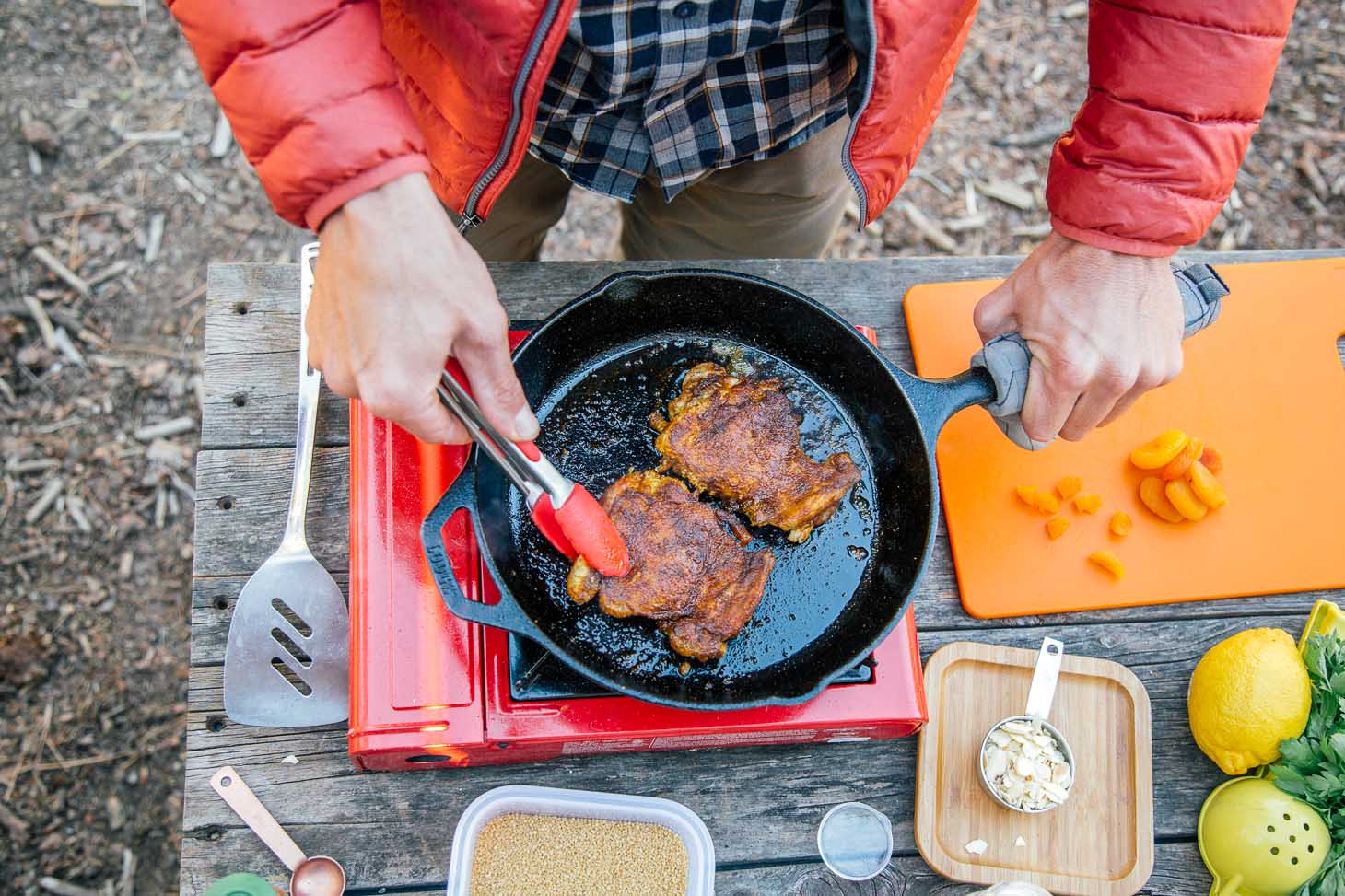 Michael cooking chicken in a cast-iron skillet over a camp stove