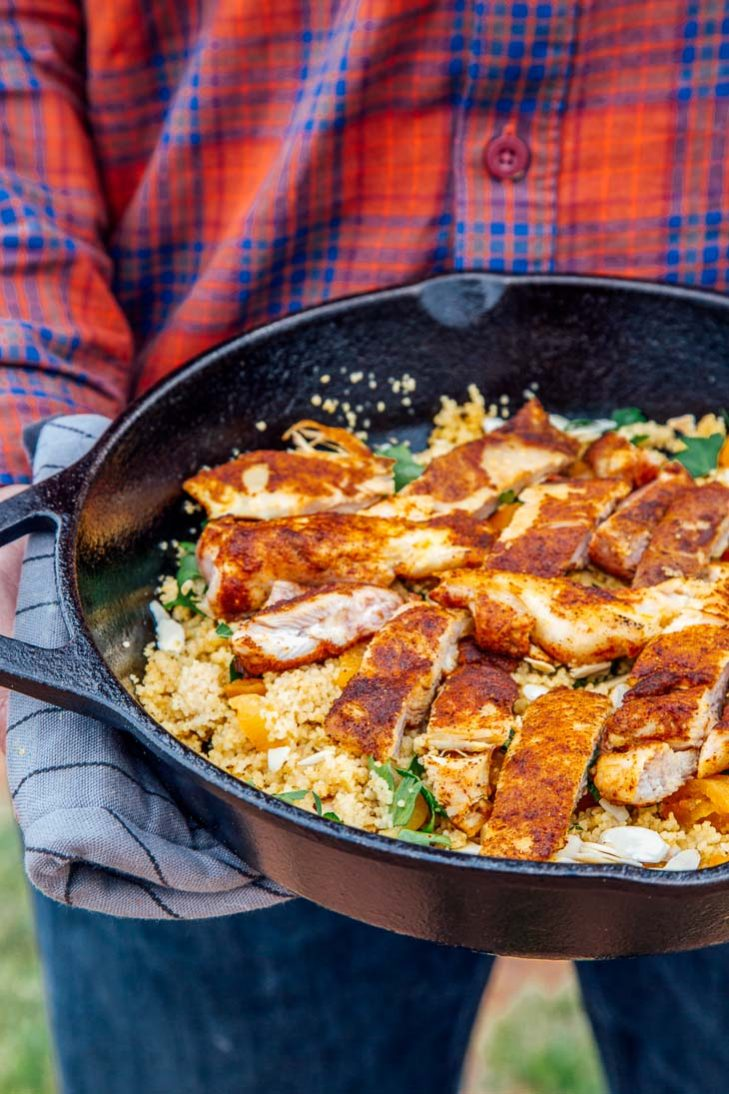 Michael holding a skillet of Moroccan spiced chicken with couscous