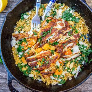 Chicken on a bed of couscous in a cast iron skillet on a camp table