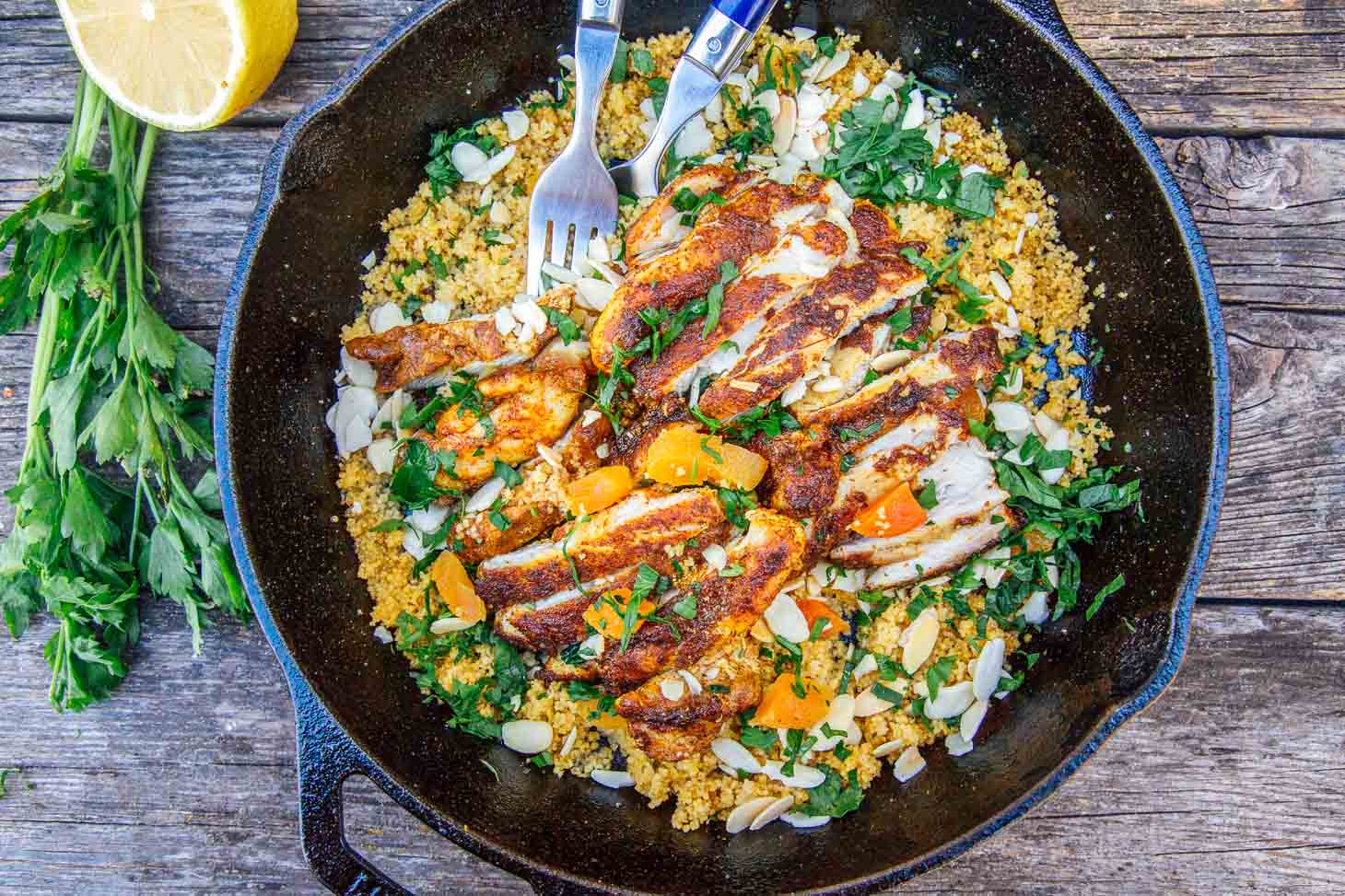 Chicken on a bed of couscous in a cast iron skillet