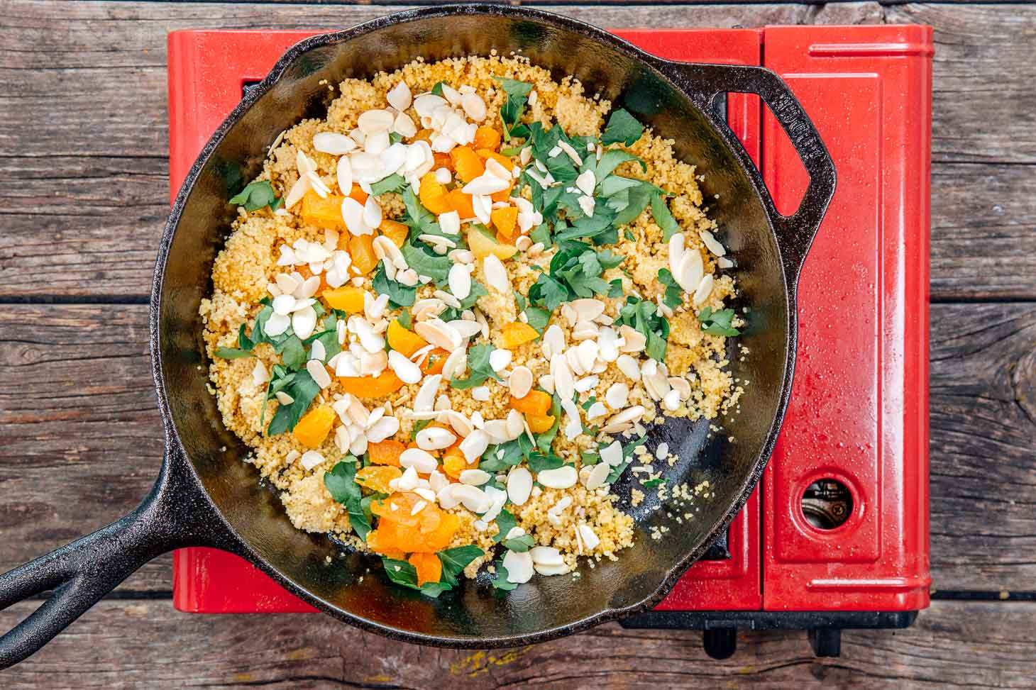 Couscous with apricots, almonds, and parsley in a cast iron skillet