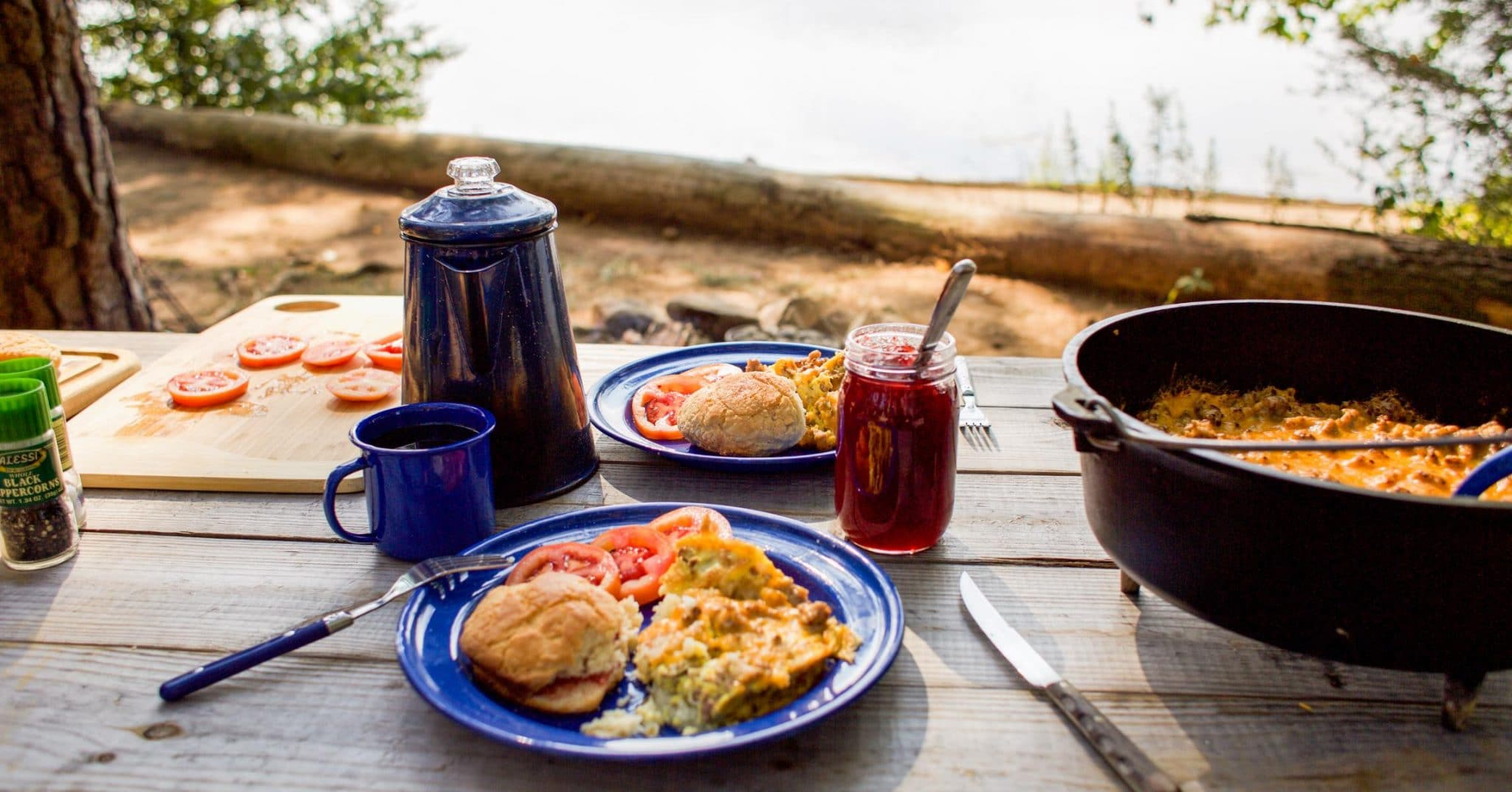 A camp scene with a pot of coffee, blue plate with egg breakfast, and Dutch oven in frame