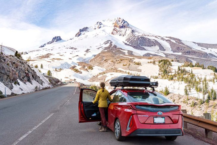 A red car is parked on the site of a road. Megan is stepping out of the car to look at Mt. Hood.