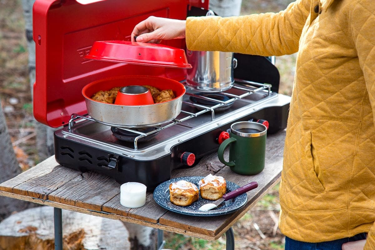 An Omnia stovetop oven on a camping stove. Megan is lifting the lid to show the cinnamon rolls inside.