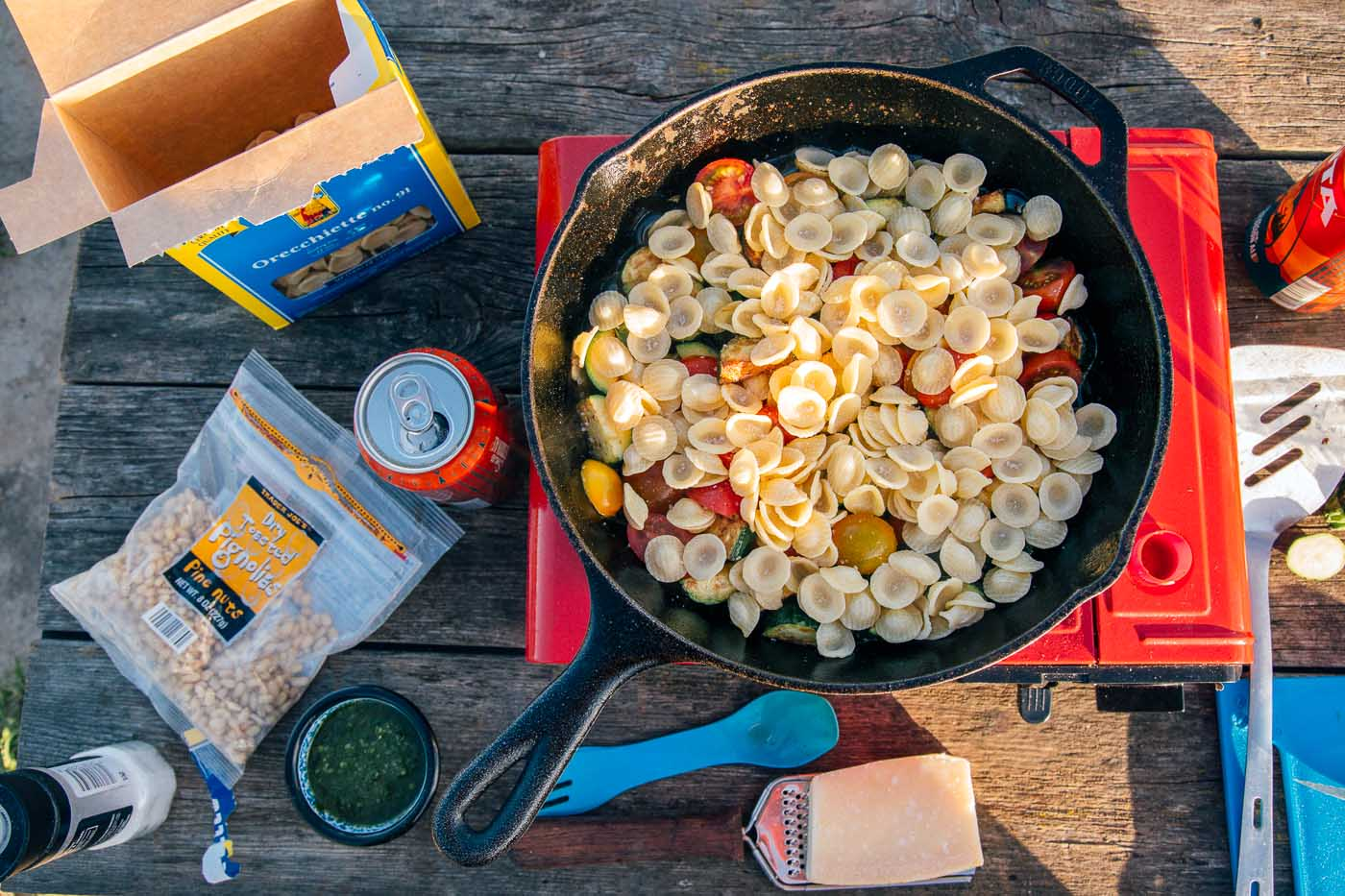 Overhead view of pasta in a cast iron skillet on a camping stove. Other pasta ingredients such as cheese, pesto, and pine nuts are on the table.