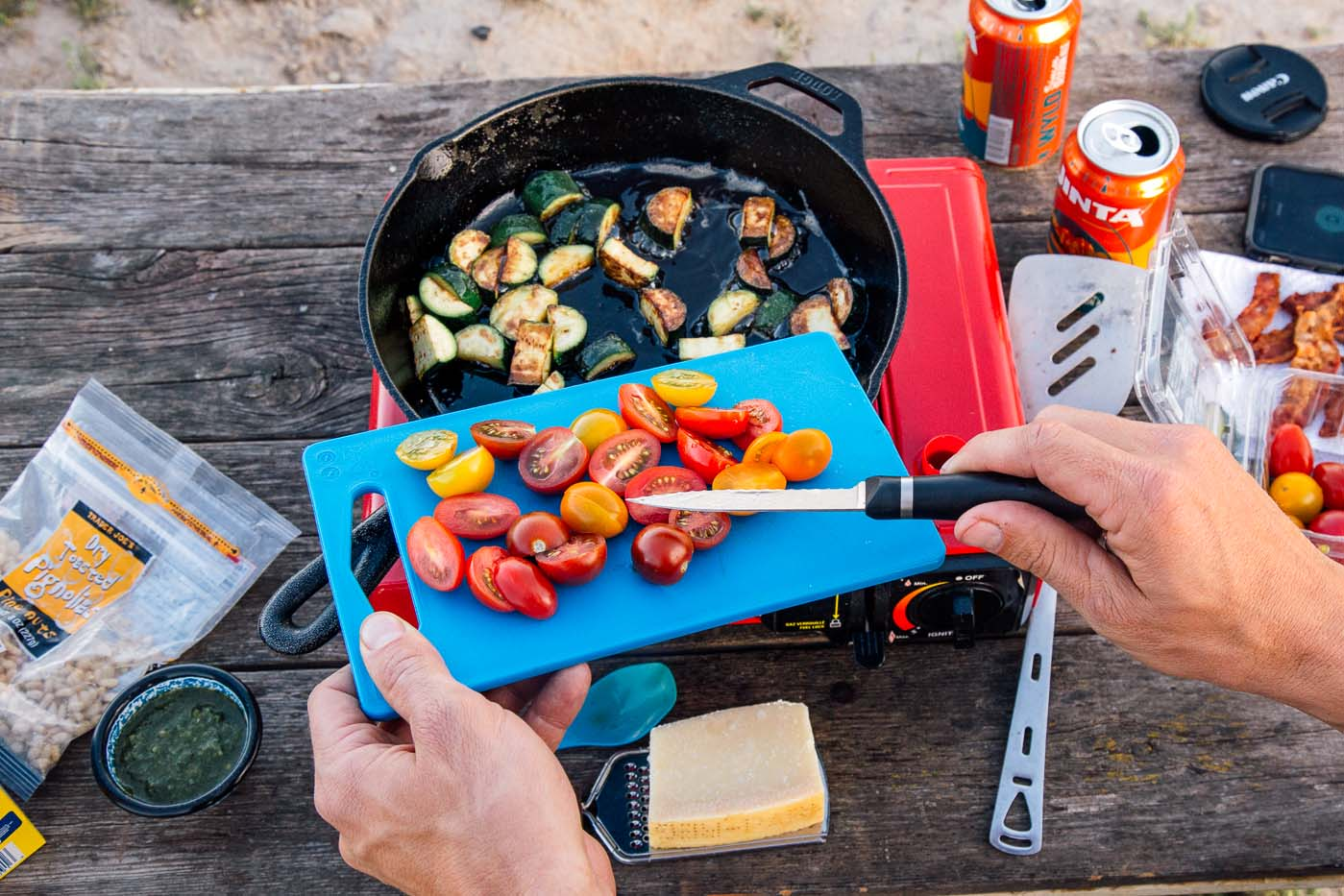 Man moving cut tomatoes from a cutting board into a cast iron skillet on a camping stove.