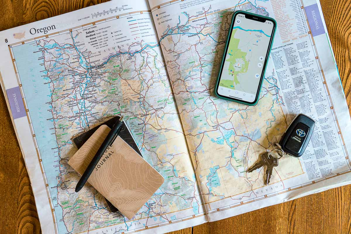 An atlas opened to show a map of Oregon. A notebook and pen, car keys, and a cell phone rest on top of the map.