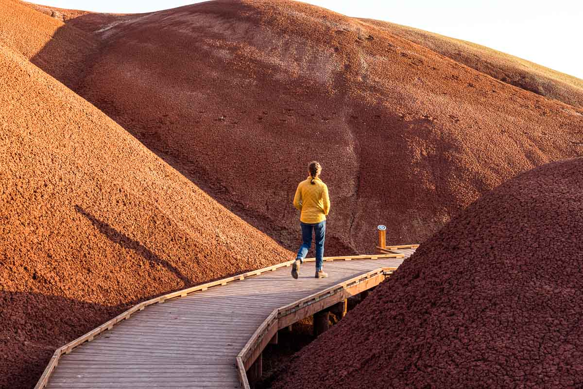 Megan walks on a boardwalk that is set between two red sand hills.
