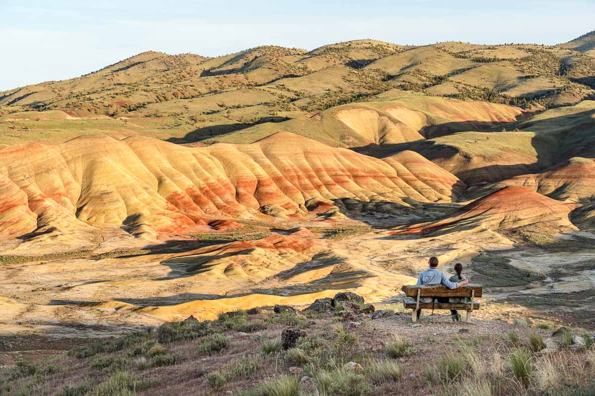 Megan and Michael sit at a bench on a overlook, looking out at the painted hills.