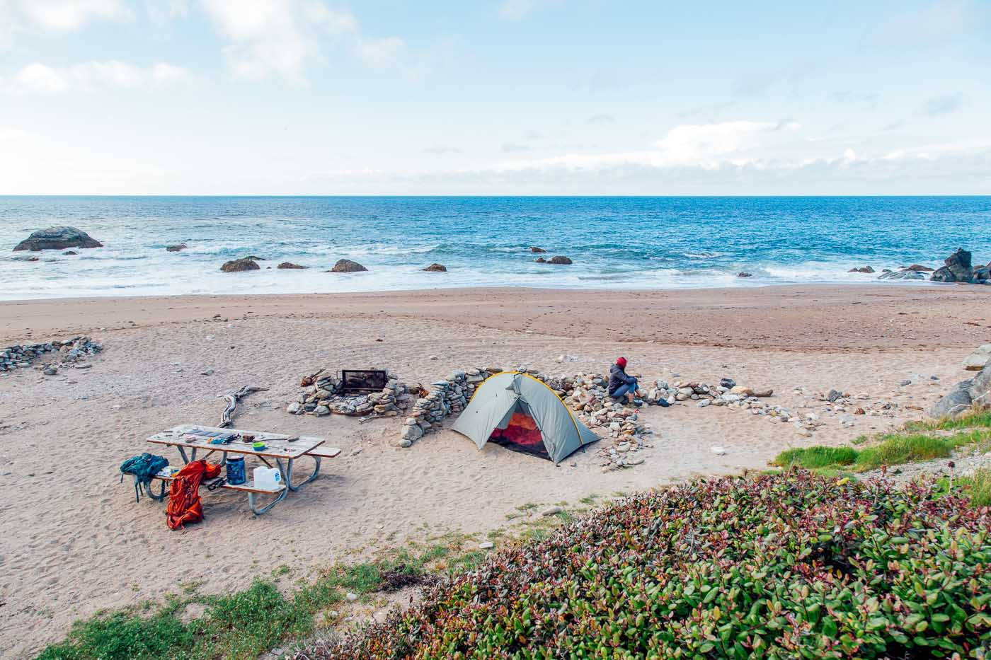 A tent set up in the sand at Parson's Landing campground with the ocean in the background.