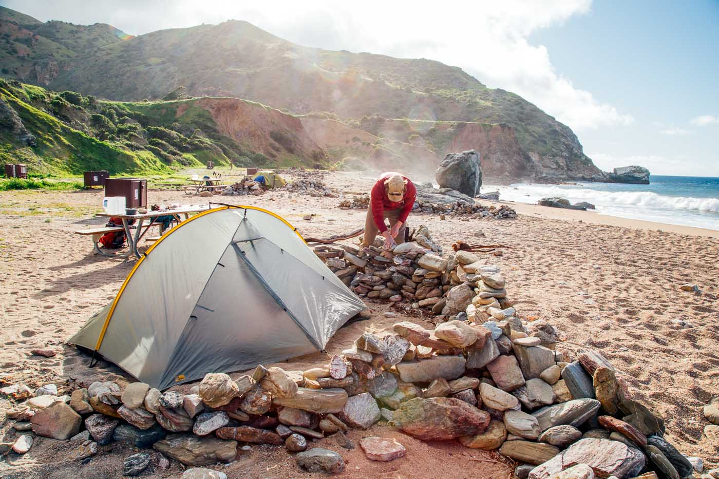 Man creating a wall of rocks around a tent.