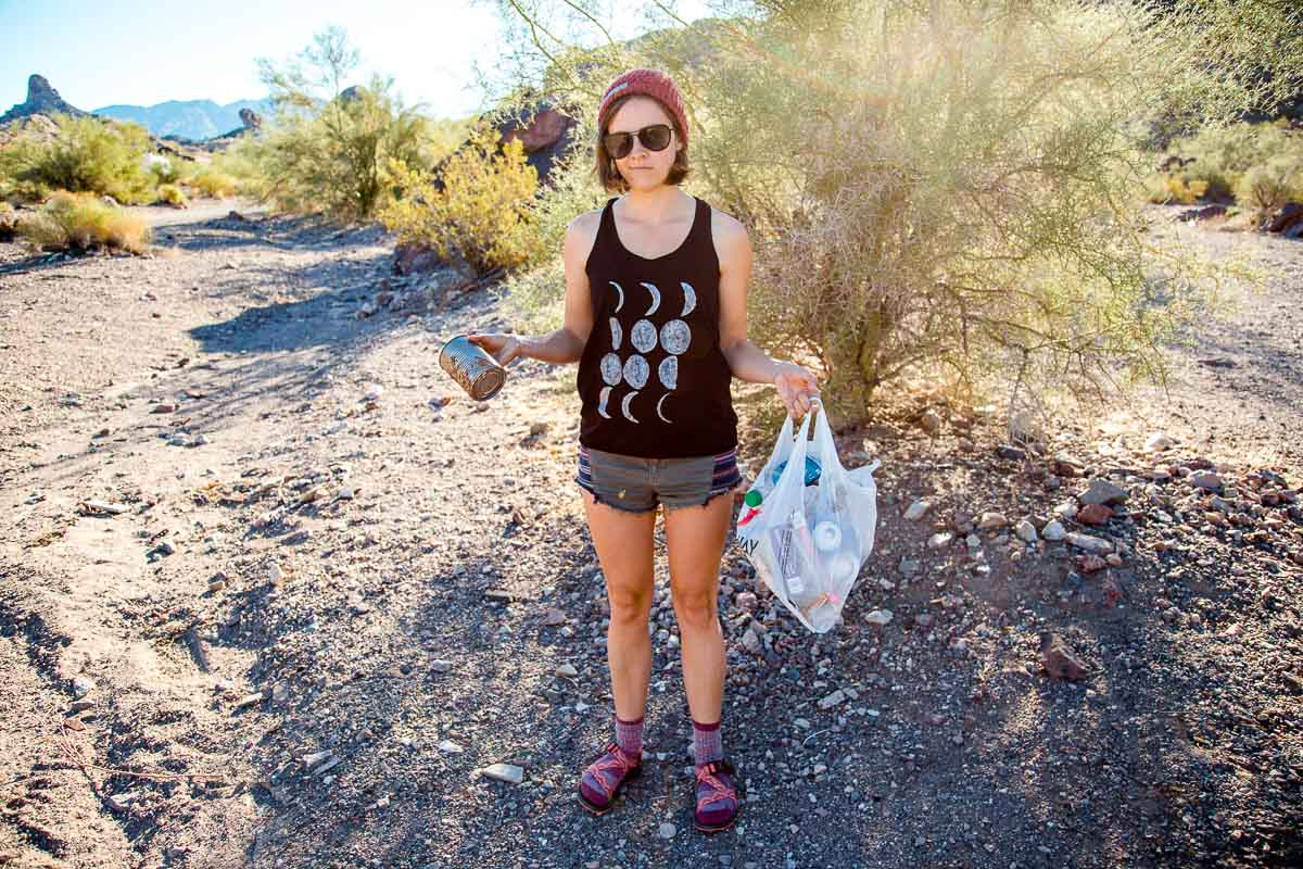 Megan is standing on a trail and is holding a piece of litter and a trash bag