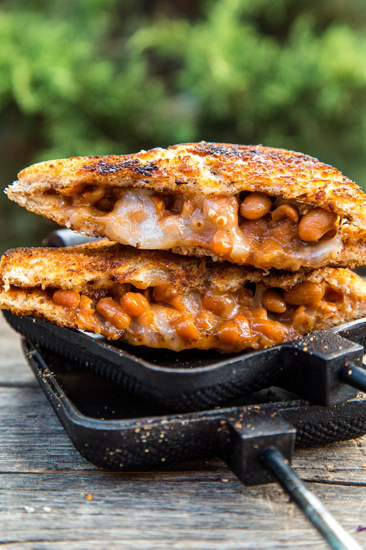 A sandwich filled with beans and cheese cut diagonally in half, resting on an open pie iron
