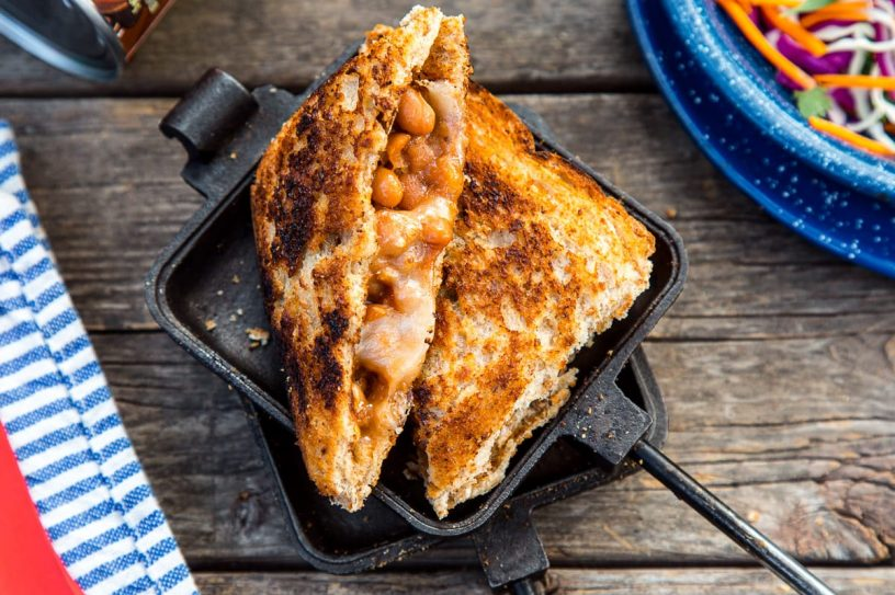 A sandwich filled with beans and cheese cut diagonally in half, resting on a open pie iron