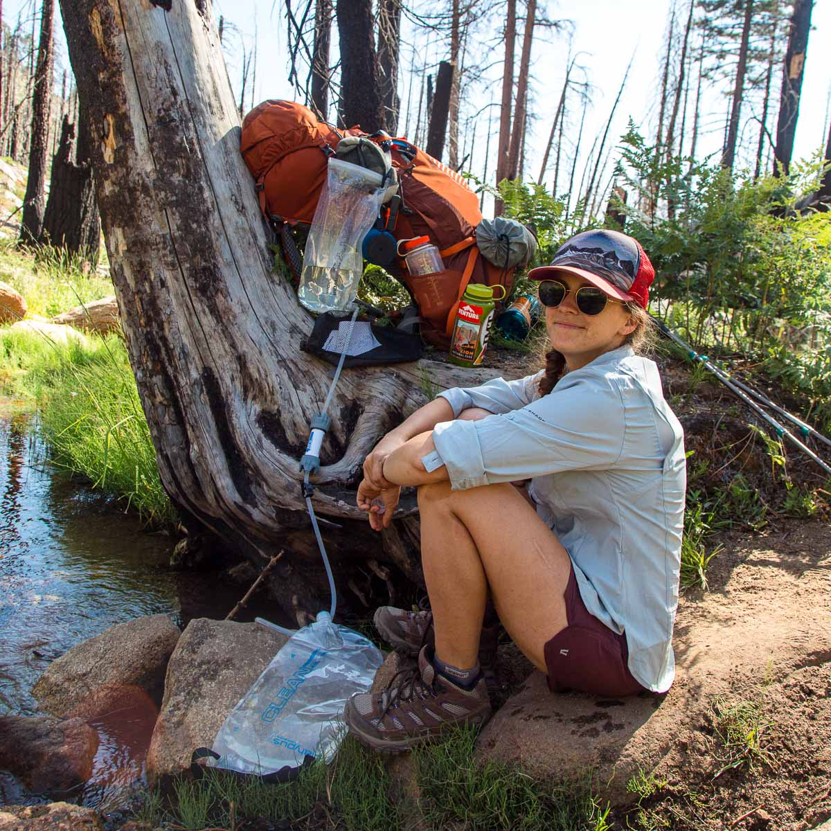 Megan sitting next to the Platypus GravityWorks water filter, which is rigged up on a tree next to a stream