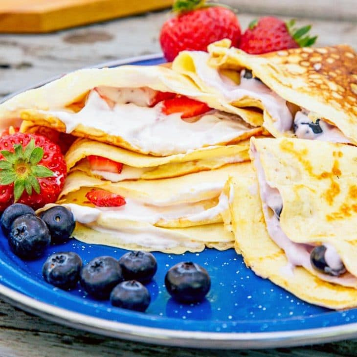 Icelandic pancakes filled with yogurt stacked on a blue plate
