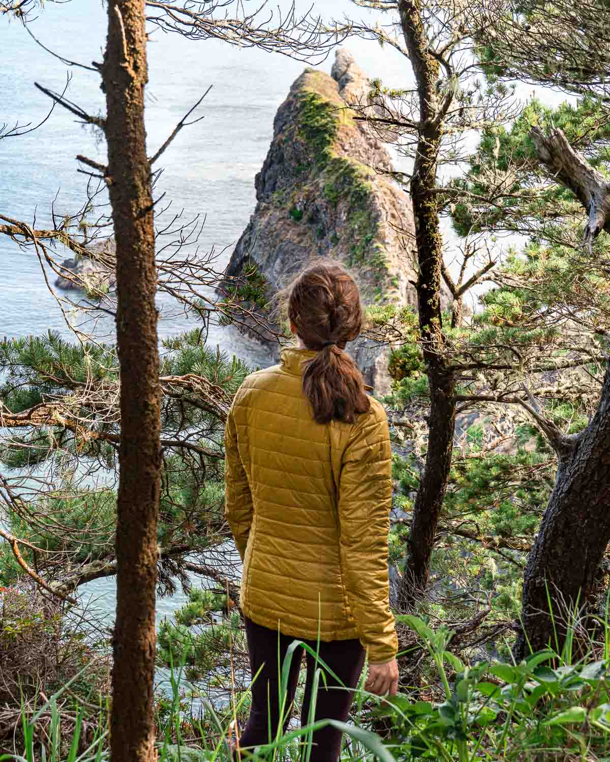 Megan stands among trees and looks out at a rock formation rising from the ocean
