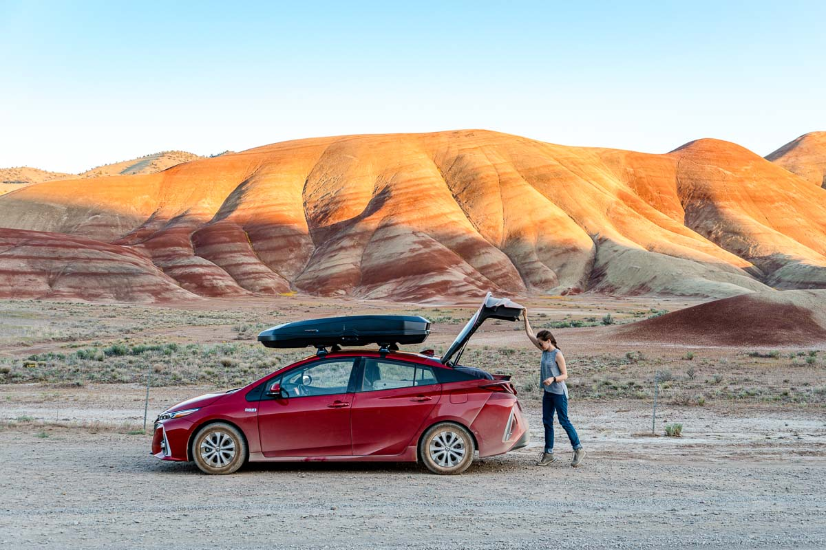 Megan is opening the trunk of a red car. The painted hills can be seen in the background.