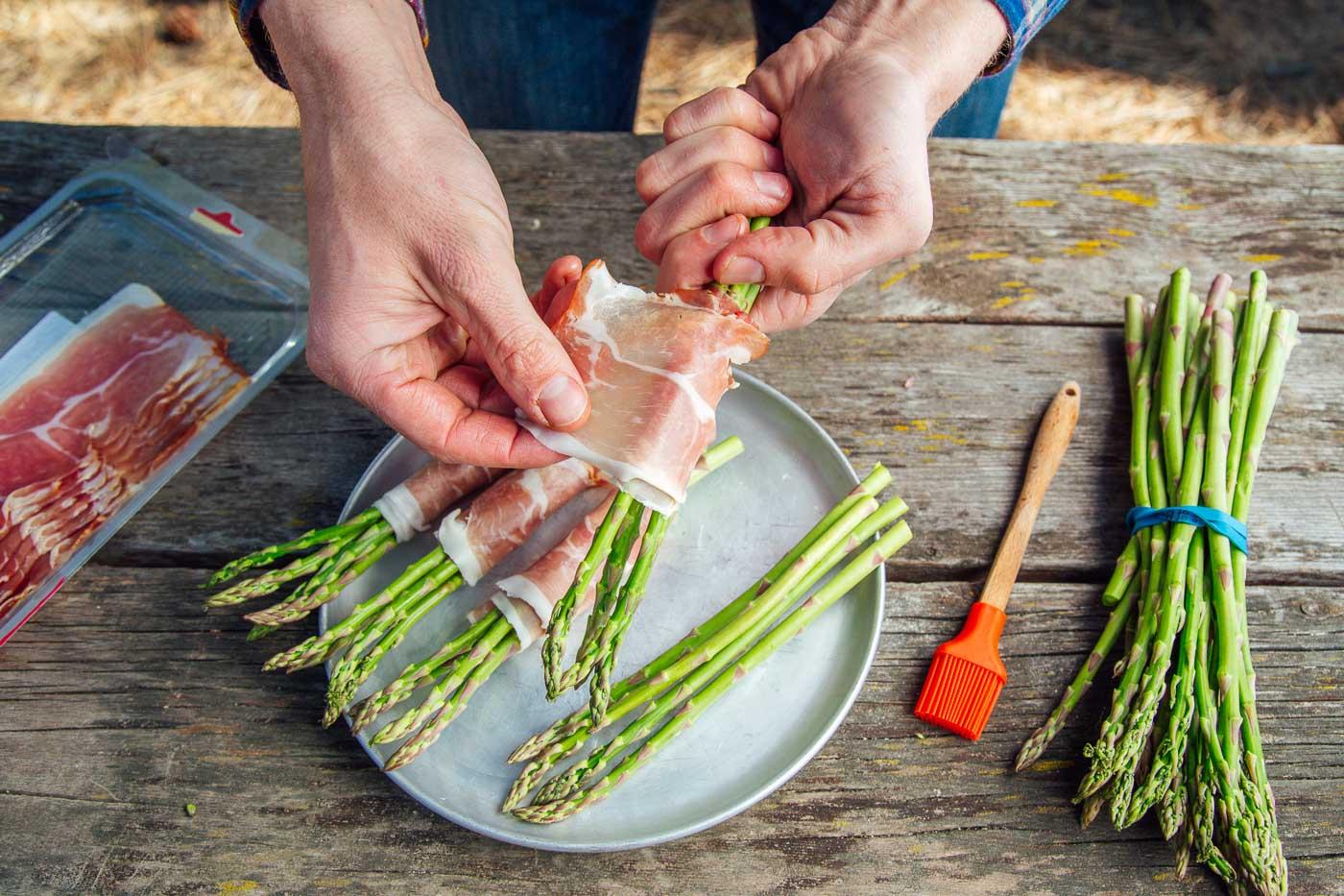 Michael wrapping prosciutto around asparagus stalks
