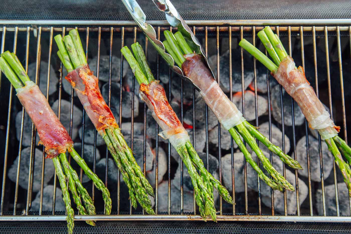 Prosciutto wrapped asparagus bundles on a grill