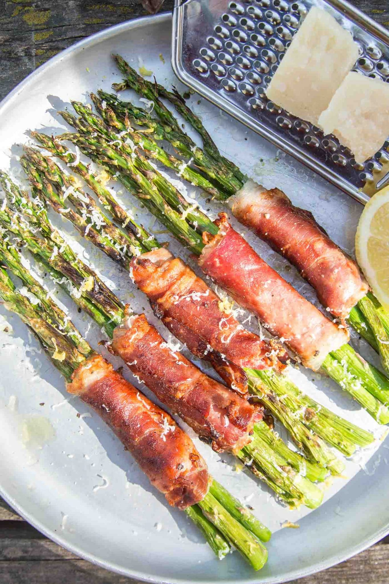 Five prosciutto wrapped asparagus bundles on a plate