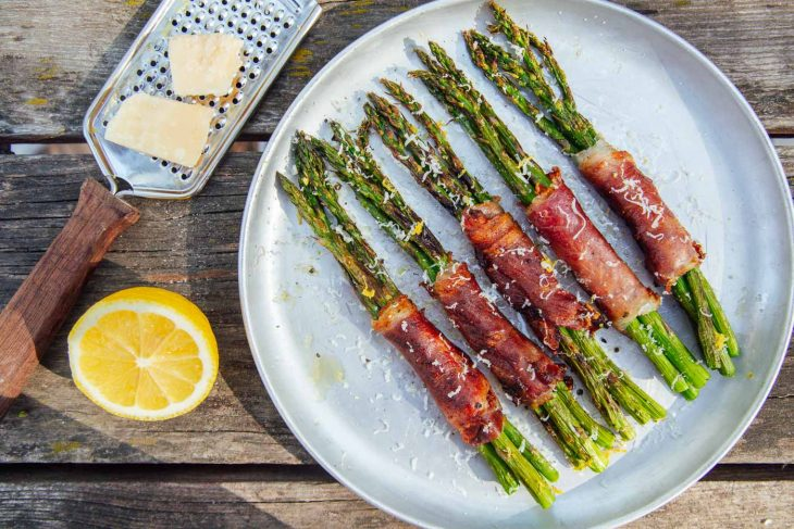 Prosciutto wrapped asparagus bundles on a plate