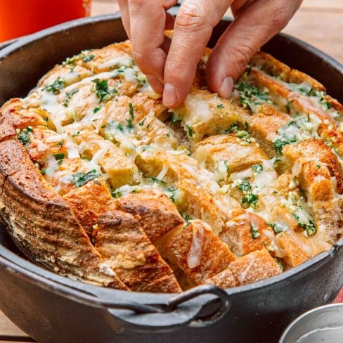 Pull apart garlic bread in a Dutch oven. a hand is reaching in to pick up a piece