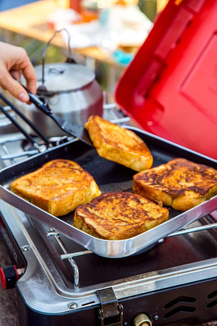 Four slices of french toast in a square skillet on a camp stove