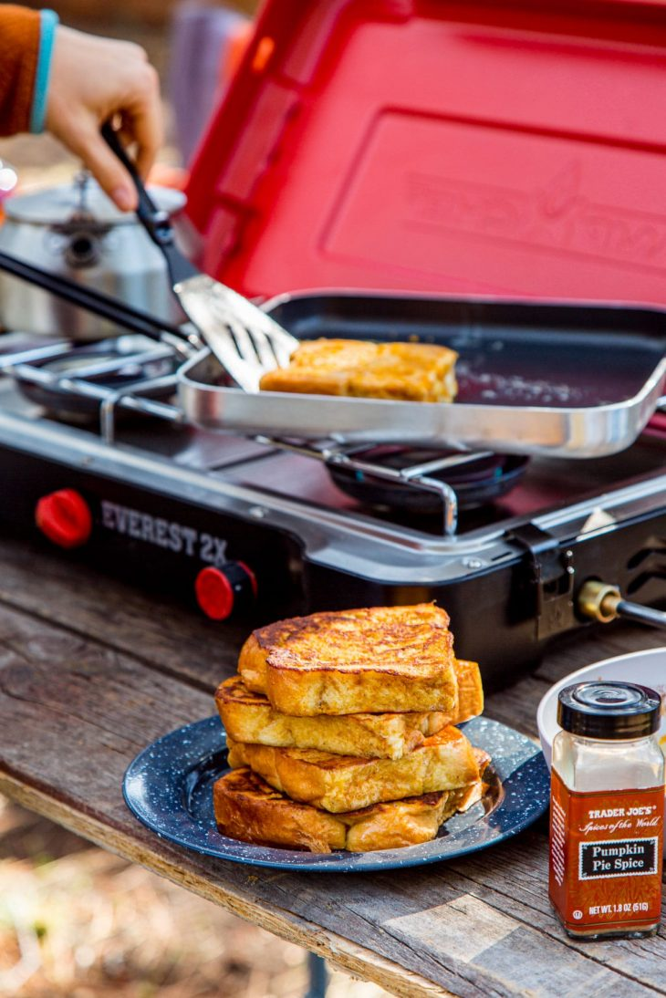 A stack of french toast on a plate next to a camp stove