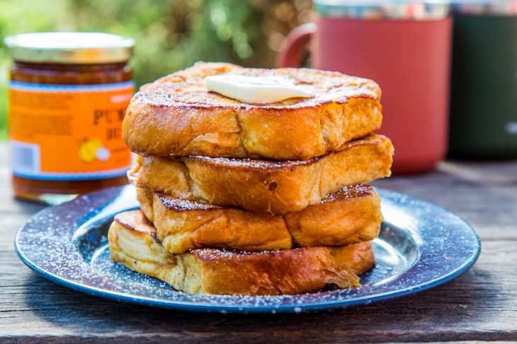 Four slices of pumpkin French toast stacked on a plate