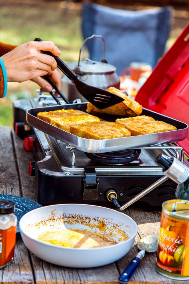 Megan flipping a slice of French toast in a skillet on a camp stove