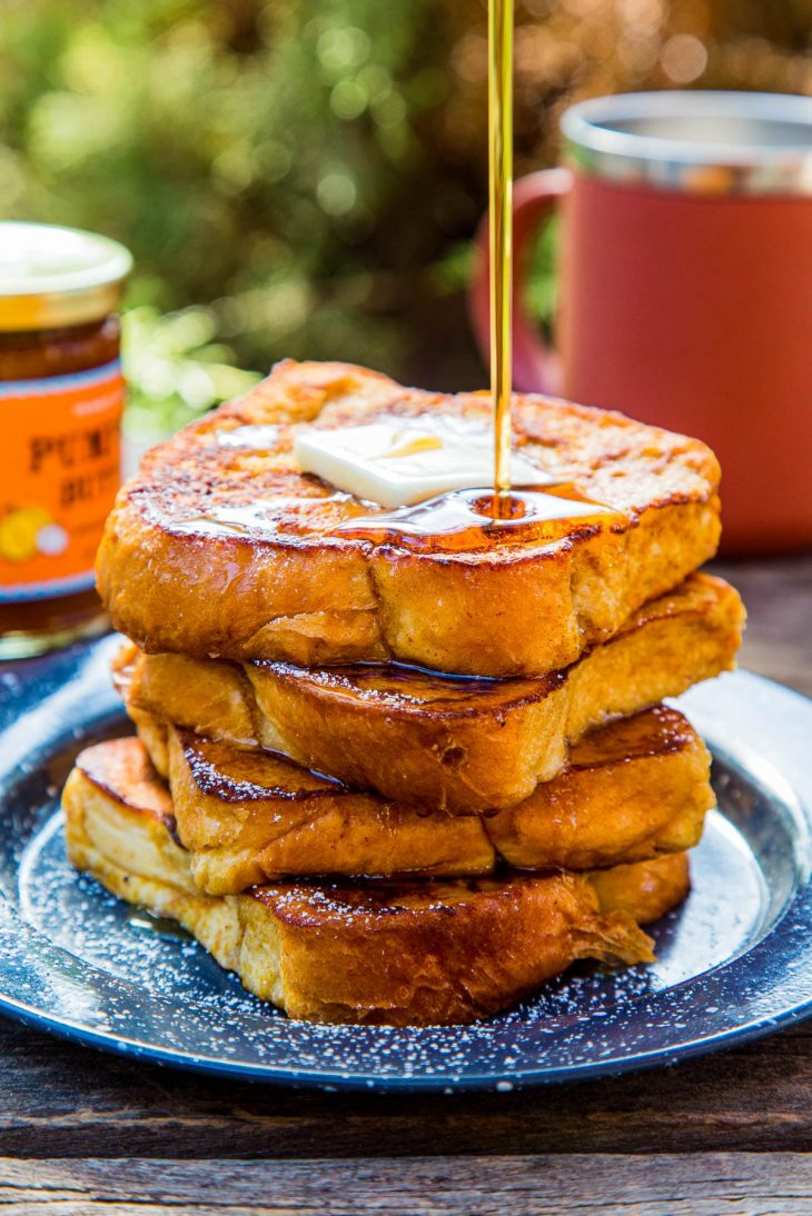 Four slices of pumpkin French toast stacked on a plate with a maple syrup drizzle