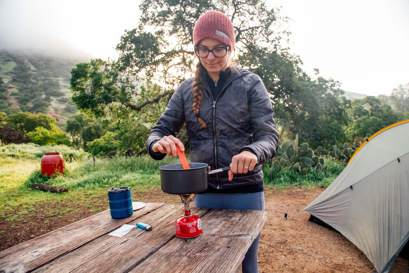 Woman cooking over a backpacking stove with a tent in the background.