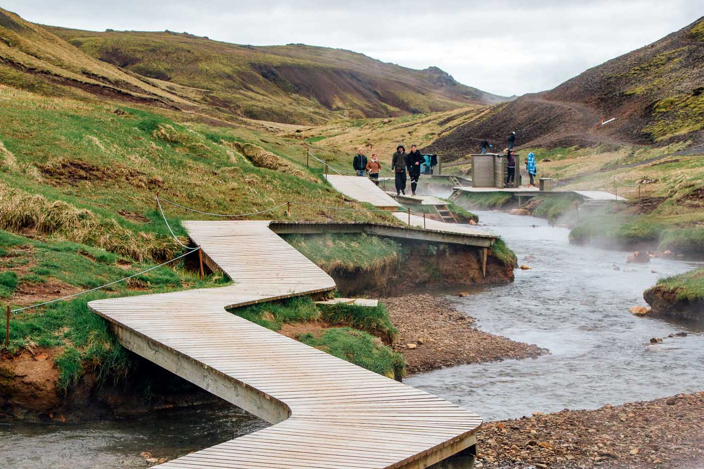 A wooden boardwalk winding around the Reykjadalur Hot Spring Thermal River