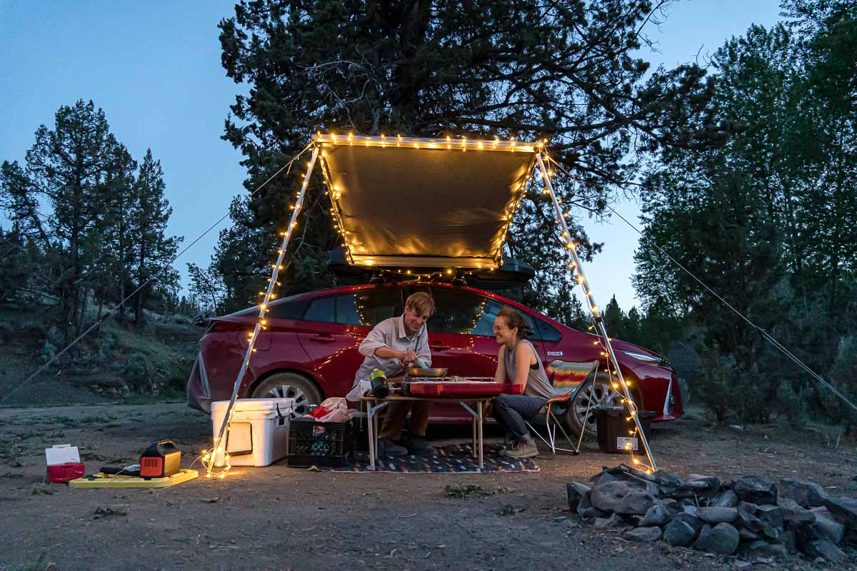 Megan and Michael sit next to a red car that has an awning set up with string lights.
