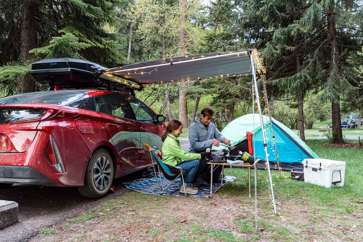 Megan and Michael sit next to a red car and are cooking on a camp stove.