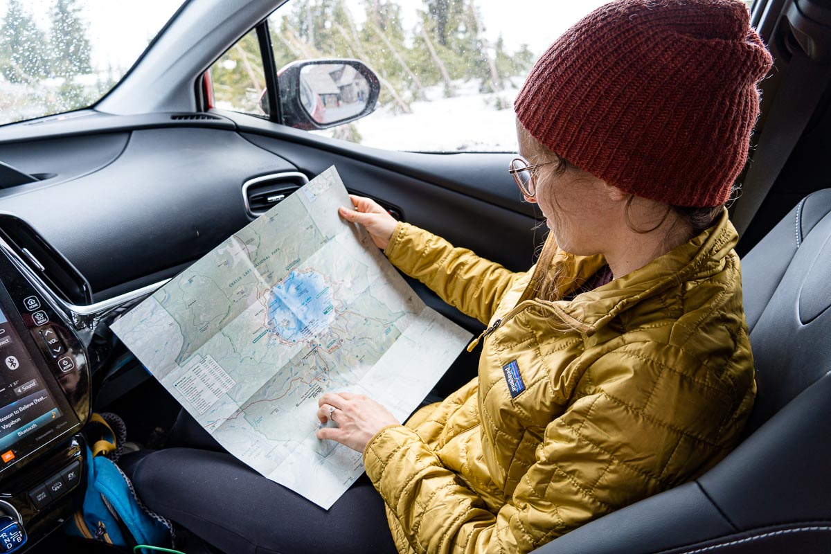 Megan is sitting in the front seat of a car looking at a map