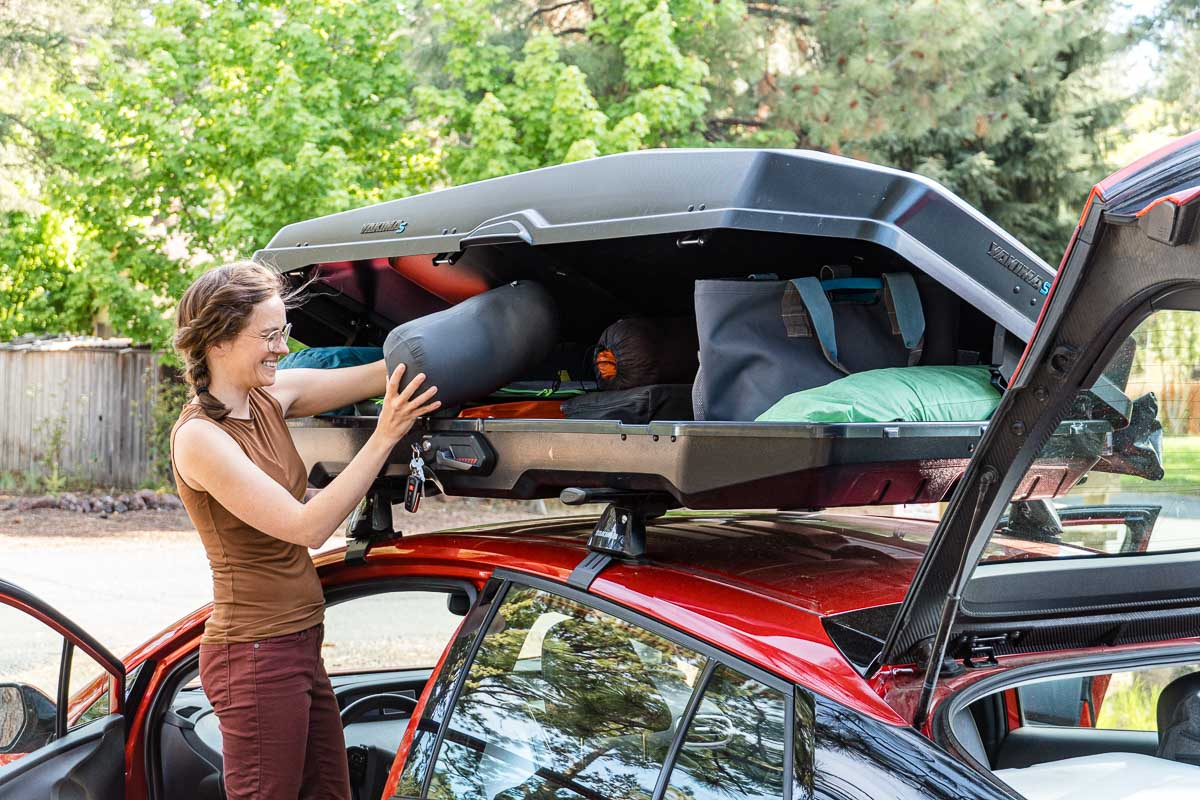 Megan stands next to a car with a roof box. She is placing a sleeping bag into the box