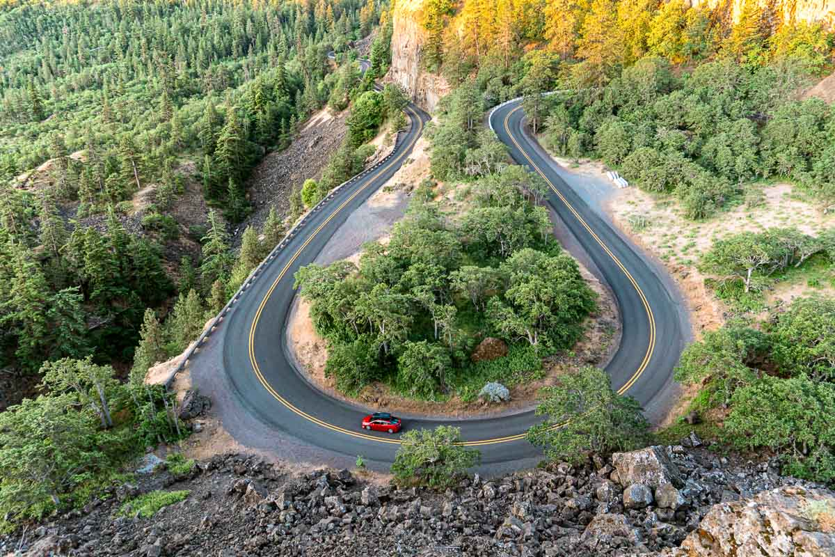 A red car driving on a U shaped road lined with trees.