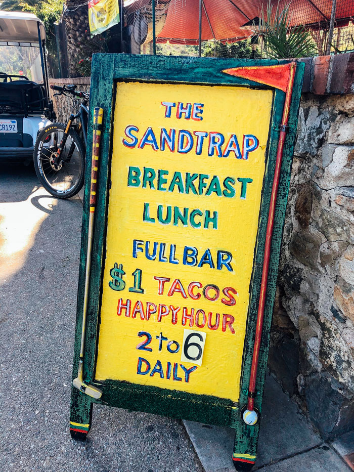 "Painted yellow sign that reads ""The Sandtrap. Breakfast, lunch, full bar. $1 Tacos Happy Hour"""