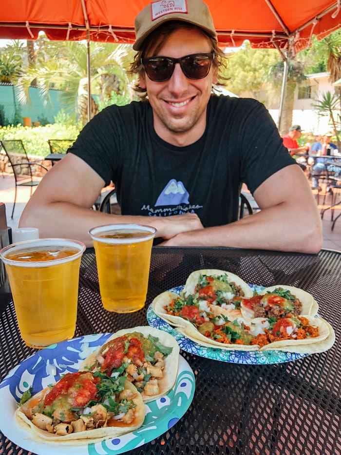 Smiling man sitting in front of a plate of tacos
