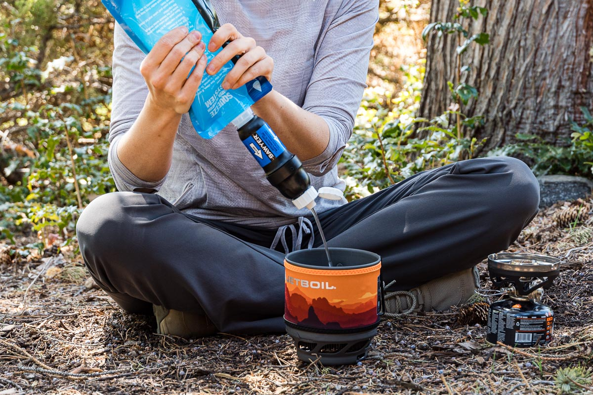 Megan is sitting on the ground and is filtering water through a Sawyer Squeeze into a jetboil pot