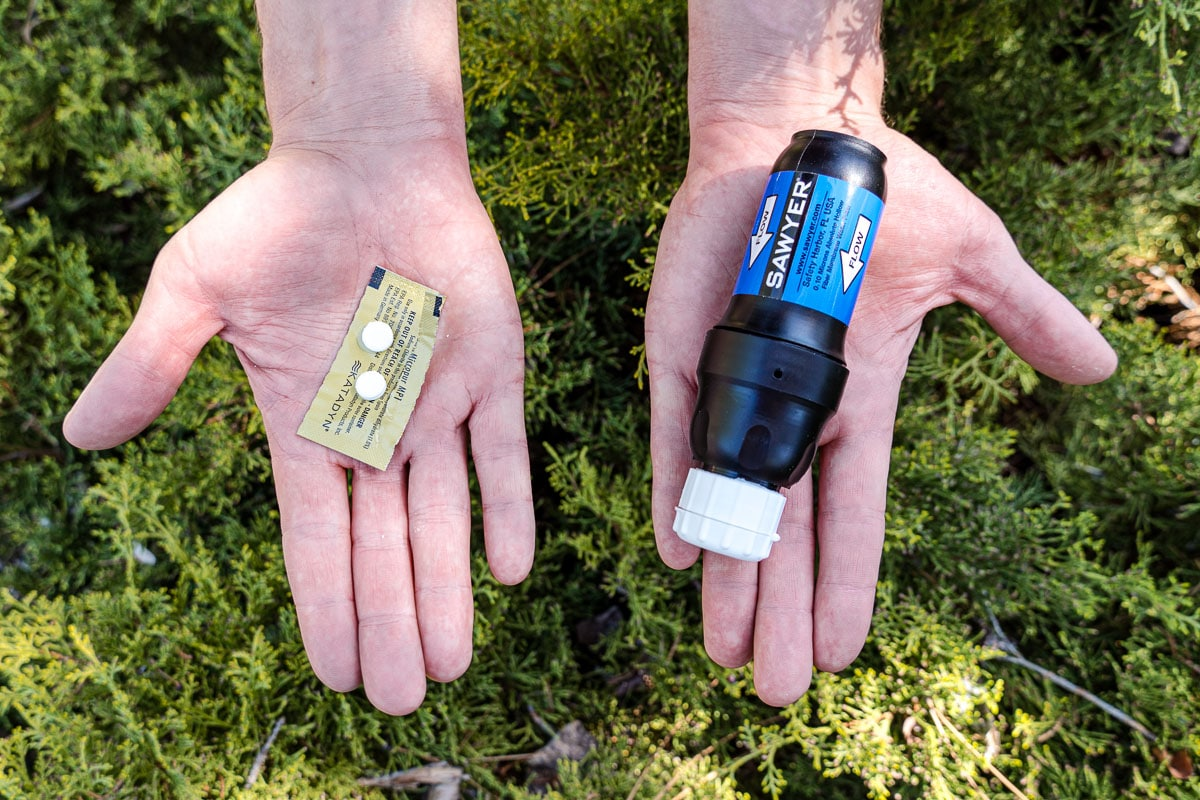 Hands, palms up, holding Micropur tablets and a sawyer squeeze water filter