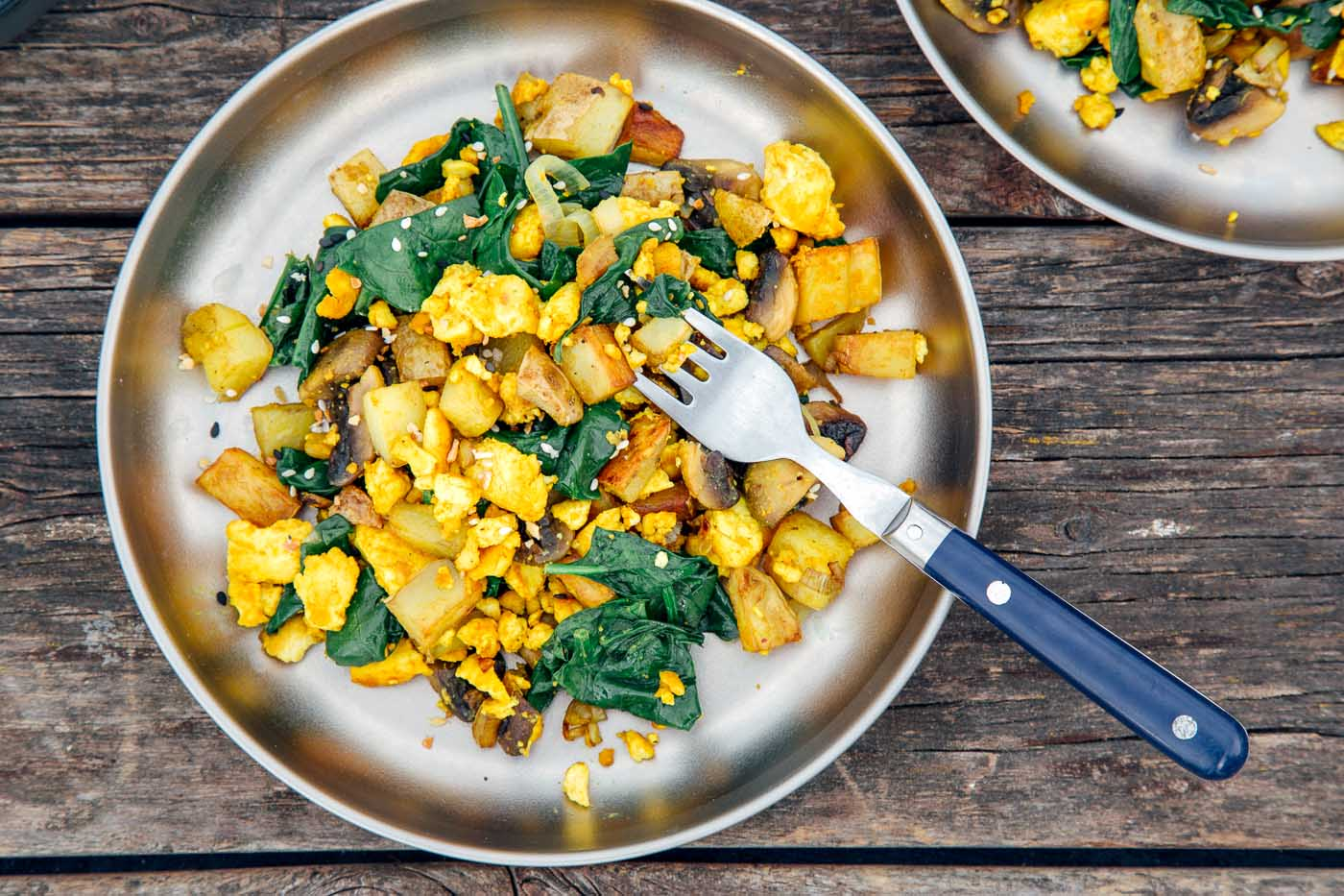 Overhead horizontal photo of a tofu scramble with spinach on a silver camping plate.
