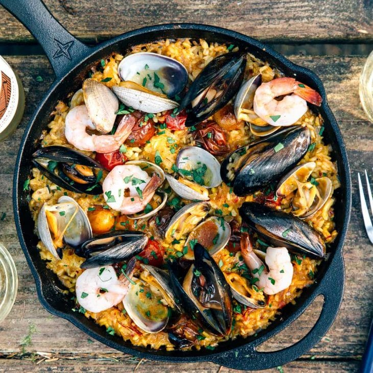 Paella topped with shrimp, mussels, and clams in a cast iron skillet on a camp table